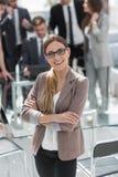 Молодая бизнес-леди на запачканной предпосылке офиса Стоковое фото RF