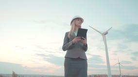 Молодая бизнес-леди на предпосылке ветрянок Девушка в шлеме планирует проект с таблеткой и видеоматериал