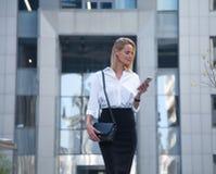 Молодая бизнес-леди перед офисным зданием используя ее сотовый телефон стоковое изображение rf