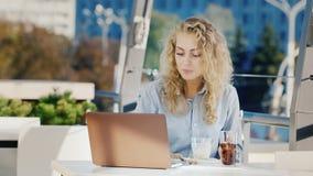 Молодая бизнес-леди работая в кафе с ноутбуком, ест мороженое На летней террасе кафа акции видеоматериалы