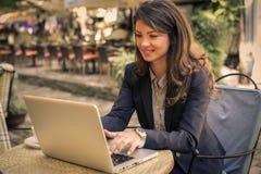 Молодая бизнес-леди работая на кафе на компьтер-книжке Стоковое Фото