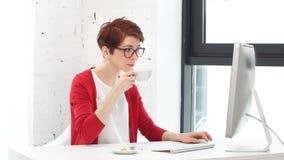 Молодая бизнес-леди работая онлайн покупки на ее офисе акции видеоматериалы