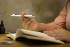 Молодая бизнес-леди работая с ручкой на офисе, она оставаясь дополнительным временем стоковые фотографии rf