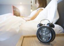 Молодая бизнес-леди сидя в белой кровати работая на портативном компьютере с будильником на переднем плане стоковое фото rf