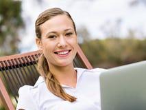 Молодая бизнес-леди сидя в парке и работая с компьтер-книжкой стоковая фотография
