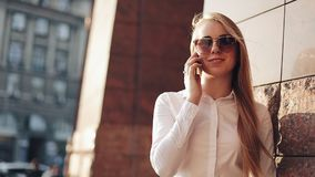 Молодая бизнес-леди стоя близко офисное здание на солнечных улицах города и говоря на передвижном сотовом телефоне акции видеоматериалы