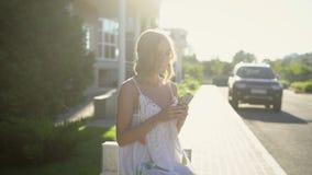 Молодая блондинка пишет к друзьям на ее мобильном телефоне, владениям дамы телефон в улице на горячий летний день сток-видео