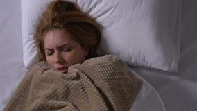 Молодая больная женщина знобя с холодом, покрывая одеяло в кровати, симптомы гриппа сток-видео