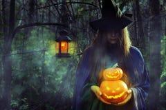 Молодая ведьма в темном лесе на хеллоуине стоковое фото rf
