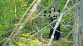 Молодая ведьма в черных одеждах связанных при цепи, пробуя освободить halloween Стиль Gothick сток-видео