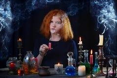 Молодая ведьма приниманнсяое за колдовство Стоковое Изображение RF