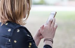 Молодая взрослая женщина используя телефон камеры как зеркало Стоковая Фотография