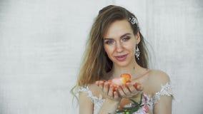 Молодая взрослая сексуальная девушка в светлом платье с лепестками розы в руках сток-видео