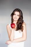 Молодая вскользь кавказская девушка с красным яблоком стоковое фото rf