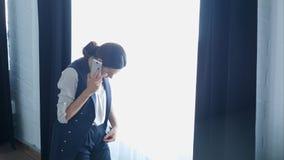 Молодая гордая коммерсантка говорит на ее мобильном телефоне с клиентом, пока стоящ близко окно офиса Стоковые Изображения RF