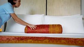 Молодая горничная кладет подушку подкладки на кровать видеоматериал