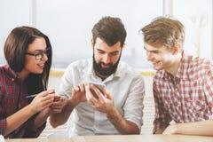 Молодая группа используя мобильный телефон Стоковая Фотография
