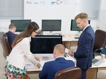 Молодая группа людей работая в офисе на компьютере стоковые фотографии rf
