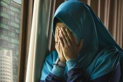 Молодая грустная и подавленная мусульманская женщина в окне шарфа головы Hijab ислама традиционном дома чувствуя нездоровую страд стоковое изображение rf