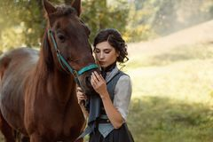 Молодая дама в годе сбора винограда одевает с длинным поездом, любяще обнимает ее лошадь с нежностью и привязанностью Старое, col стоковые фото