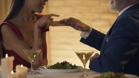 Молодая дама давая поцелуй воздуха ее старому рекламодателю в обмен на золотую карту, деньги сток-видео