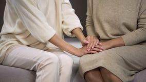Молодая дама держа и штрихуя руку старшей женщины, утихомиривать и поддерживать стоковая фотография