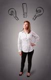 Молодая дама думая с вопросительными знаками наверху Стоковое Фото