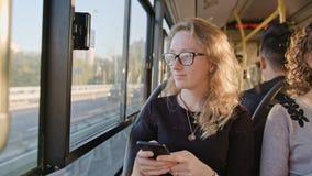 Молодая дама используя Smartphone на шине Стоковые Изображения