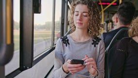 Молодая дама используя Smartphone на шине Стоковое Изображение RF