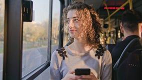Молодая дама используя Smartphone на шине Стоковые Фото