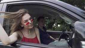 Молодая дама перемещений пар на автомобиле в красных рубашке и солнечных очках показывает что ее человек tounge управляет корабле акции видеоматериалы