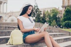 Молодая дама пишет сообщение на ее pda пока на прогулке снаружи стоковые изображения