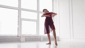 Молодая дама представляя элегантную хореографическую комнату в студии современного танца сток-видео