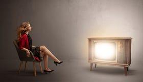 Молодая дама смотря к винтажному телевидению стоковые изображения rf