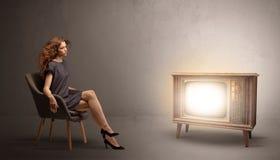 Молодая дама смотря к винтажному телевидению стоковое фото rf