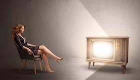 Молодая дама смотря к винтажному телевидению стоковая фотография