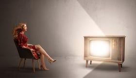 Молодая дама смотря к винтажному телевидению стоковое изображение