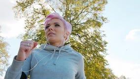 Молодая дама с розовыми волосами Jogging в пригородах glitch акции видеоматериалы