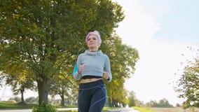 Молодая дама с розовыми волосами Jogging в пригородах glitch сток-видео