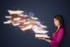 Молодая дама читая книгу при листы летания приходя из книги Стоковые Фото