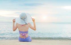 Молодая девушка бикини сидя на белом песке стоковые фото