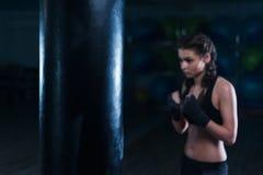 Молодая девушка боксера бойца в тренировке с тяжелой грушей Стоковое Изображение RF