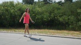 Молодая девушка брюнета в наушниках идя через парк Sportive девушка в розовые верхние усмехаться и танцах в парке Привлекательный видеоматериал