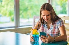 Молодая девушка брюнета подростка с длинный сидеть волос крытый в городском кафе, выпивает голубой коктейль лимонада и использует стоковые фото