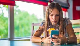 Молодая девушка брюнета подростка с длинный сидеть волос крытый в городском кафе, выпивает голубой коктейль лимонада и использует стоковая фотография rf