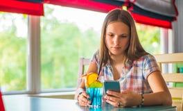 Молодая девушка брюнета подростка с длинный сидеть волос крытый в городском кафе, выпивает голубой коктейль лимонада и использует стоковые изображения