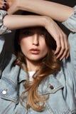 Молодая девушка брюнета с длинными пропуская волосами одетыми в представлениях куртки джинсов держа ее руки на ее голове на темно стоковое фото rf