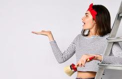 Молодая девушка брюнета с щеткой и лестницей - показывает космос для вашей рекламы стоковые изображения rf