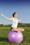 Молодая девушка брюнет выполняя йогу Стоковые Изображения