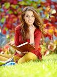 молодая девушка брюнет читая книгу Стоковые Фотографии RF